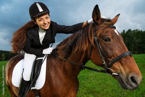 Beautiful smiling girl sitting on a horse outdoors