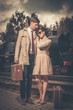 Beautiful couple with suitcases on train station platform