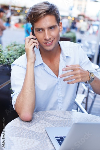 Handsome young man with laptop and mobile phone