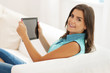 Happy young woman using digital tablet in living room