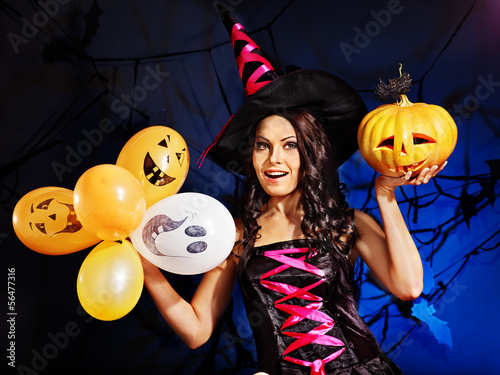 Happy woman holding pumpkin and balloon.