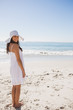 Brunette in white sunhat and dress looking over her shoulder at
