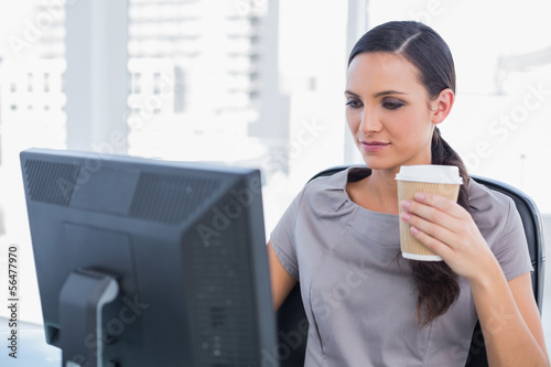Attractive businesswoman holding coffee and working