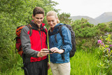 Happy couple on a hike looking at photo on smartphone
