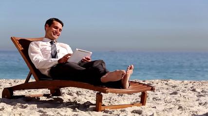Businessman lying on the beach