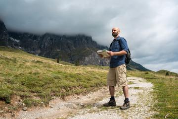 Mann mit Rucksack und Wanderkarte in den Bergen