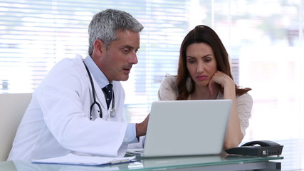 Doctor explaining a patient disease with a laptop