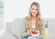 Smiling pretty blonde eating strawberries sitting on cosy sofa