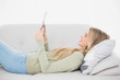 Smiling pretty blonde using her tablet lying on cosy sofa