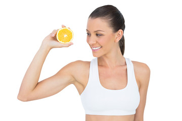 Smiling woman in sportswear holding orange slice
