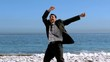 Cheerful free businessman dancing on the beach