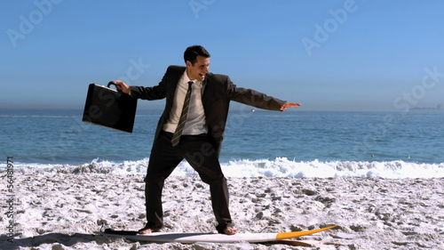 Smiling businessman balancing on a surfboard