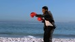 Handsome businessman boxing on the beach