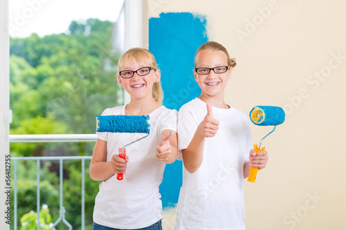 Girls painting a wall in the family home