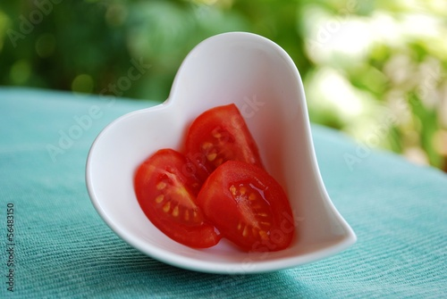 Red tomatoes salad in heart shape bowl on green background