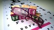 Pink glasses falling next to blocks spelling out eye test