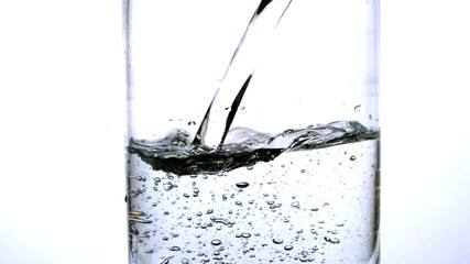Water being poured into a glass on white background