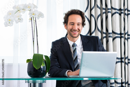 businessman in hotel working on laptop