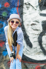 Smiling hipster girl with retro photo camera against urban wall