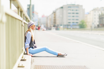 Hipster girl sitting on city street
