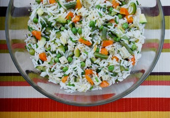 Vegetarian rice salad in a glass bowl on colorful background