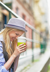 Smiling hipster girl with cup of hot beverage on city street