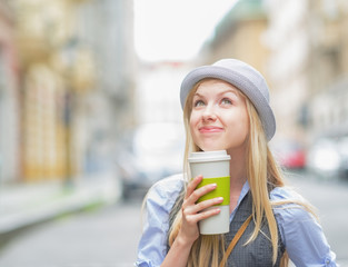 Thoughtful hipster girl with cup of hot beverage on city street