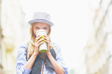 Hipster girl drinking hot beverage on city street