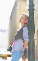 Happy hipster girl listening music on city street