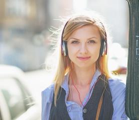 Portrait of happy girl listening music on city street