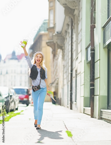 Happy tourist girl with map walking on city street