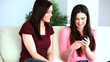 Women sitting on couch and using a mobile phone