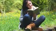 Woman sitting on grass reading a book