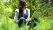 Woman sitting on grass using her laptop