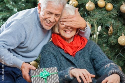 Man Surprising Senior Woman With Christmas Gifts