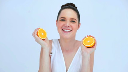 Attractive woman holding slices of orange