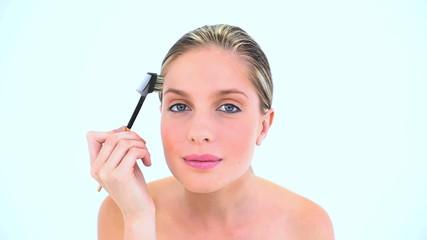 Attractive woman brushing her eyebrow