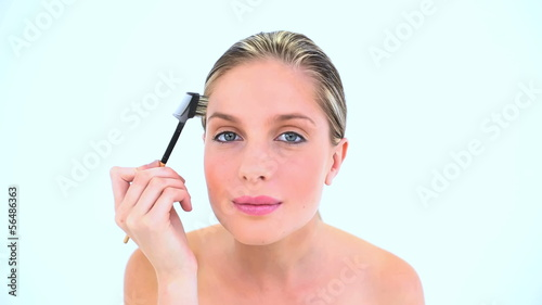 Attractive woman brushing her eyebrow