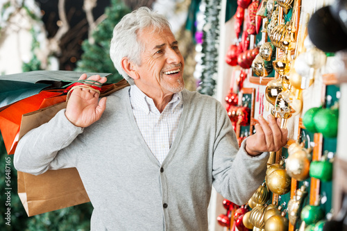 Senior Man Buying Christmas Ornaments At Store