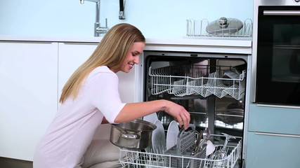 Blonde woman put her dishes in dishwasher in kitchen