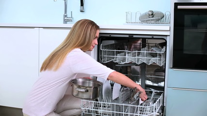 Unsmiling blonde woman put her dishes in dishwasher in kitchen