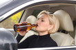 Woman alcoholic drinking as she drives the car
