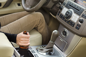 Woman alcoholic with a bottle of booze in the car