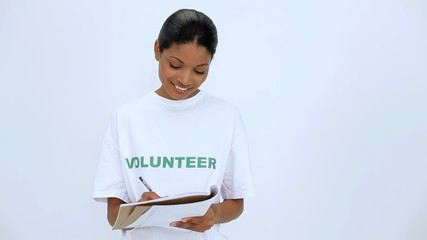 Smiling volunteer woman thinking and writting on notebook