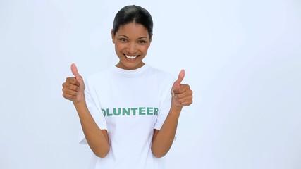 Smiling volunteer woman does a thumbs up at camera