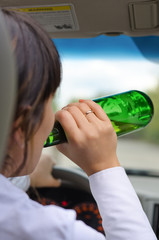 Woman driver drinking while driving on a road