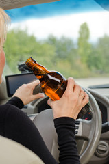Woman driving holding a bottle of alcohol