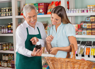 Senior Salesman Assisting Female Customer In Shopping Groceries