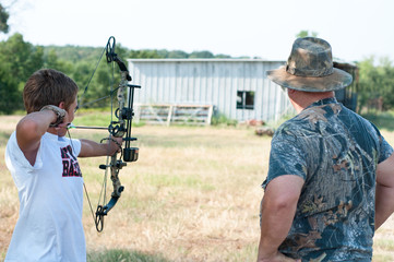 Teen boy with grandpa shooting bow