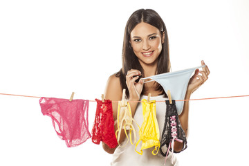 Attractive young woman hanging up her  underwear on clothesline